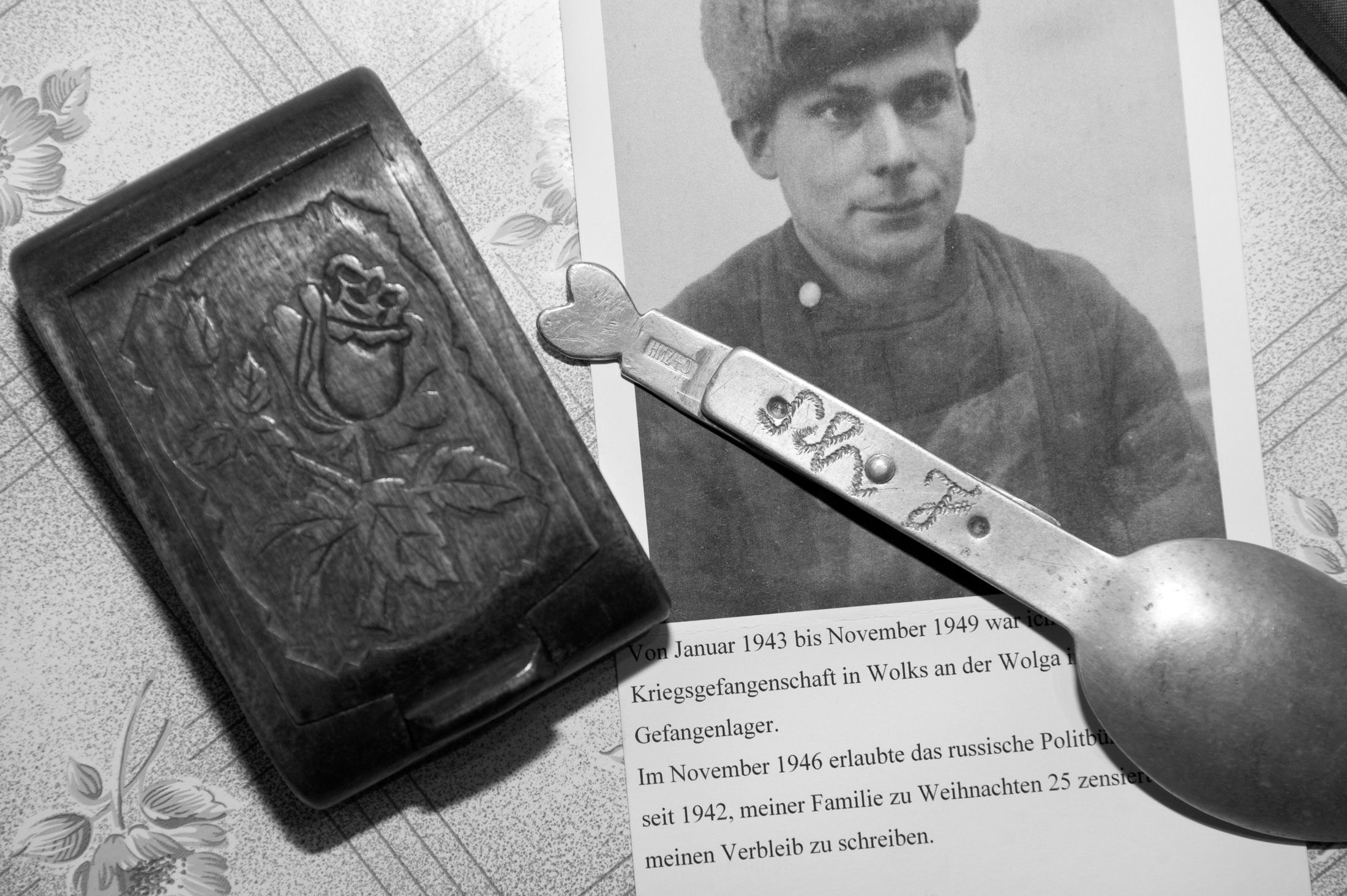 Photograph showing Scheins as a POW, along with a tin spoon bearing his initials and a wood carving he made in Soviet captivity